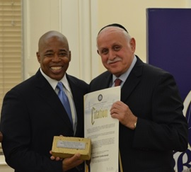 "Brooklyn Borough President Eric Adams (left) presents Dr. Robert Goldschmidt, executive dean of the Lander College of Arts and Sciences in Flatbush and Touro's vice president for planning and assessment, with a citation and gold-plated cornerstone brick, symbolizing his numerous contributions to the community and to the building of ""One Brooklyn."""
