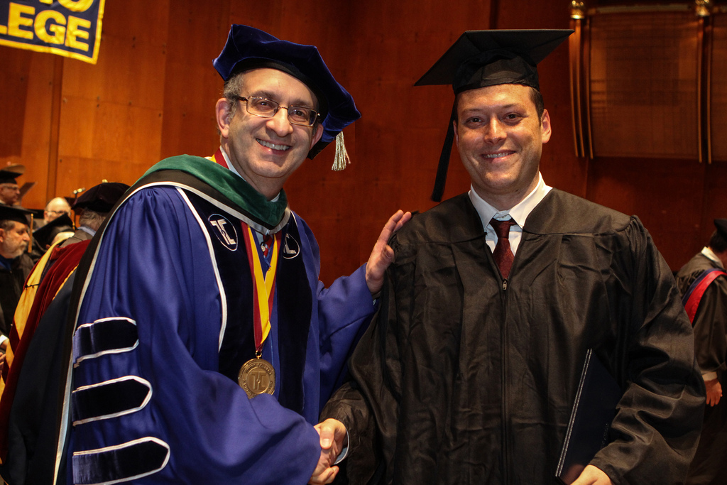 Joseph Reich of Brooklyn, N.Y. (right) shakes hands with Dr. Alan Kadish, president and CEO of the Touro College and University System, at the Lander College commencement exercises at Avery Fisher Hall. Reich was named the 2013 valedictorian of the men's division of the Lander College of Arts & Sciences in Flatbush.